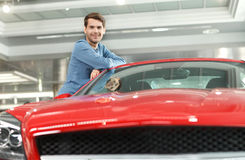 Happy car ownner. Handsome young men leaning on his new car at t Stock Photo