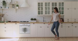 Happy carefree active girl dancing alone in modern kitchen interior