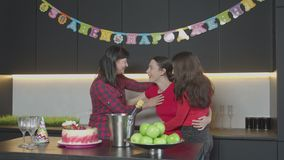 Cheerful women embracing, kissing at birthday party. Happy carefree birthday girl enjoying embrace and kisses of mother and best friend during celebration of stock video