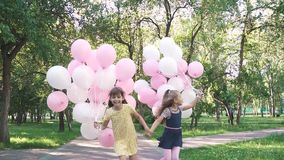 A happy carefree childhood. two little girlfriends holding hands and running through the summer Park holding colorful stock footage