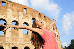 Happy carefree elated travel woman by Colosseum. Rome, Italy with arms raised out and up in ecstatic happiness expression. Travel concept with beautiful mixed Stock Photo