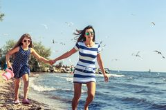 Happy carefree family running on beach at sea. Coast. Little girl kid with mother having fun. Summer holidays vacation. Happiness royalty free stock image
