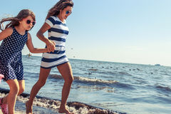 Happy carefree family running on beach at sea. Happy carefree family running on beach at sea coast. Little girl kid with mother having fun. Summer holidays stock photo