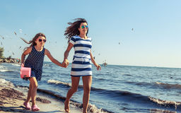 Happy carefree family running on beach at sea. Happy carefree family running on beach at sea coast. Little girl kid with mother having fun. Summer holidays royalty free stock photography