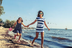 Happy carefree family running on beach at sea. Happy carefree family running on beach at sea coast. Little girl kid with mother having fun. Summer holidays royalty free stock photo