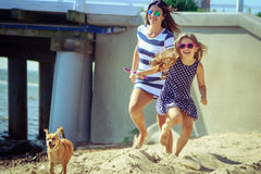 Happy carefree family running on beach at sea. Happy carefree family with dog running on beach at sea coast. Little girl kid with mother having fun. Summer royalty free stock photography