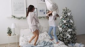 Happy carefree mom and preschool girl enjoy a funny pillow fight on the bed. Mom and daughter tripled the pillow