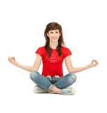 Happy and carefree teenage girl in lotus pose Stock Photo