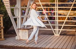 Happy carefree woman in blue clothes dancing on street in sunset. royalty free stock photo