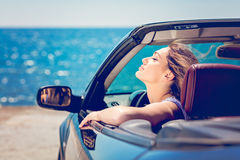 Happy and carefree woman in the car on the beach Royalty Free Stock Photos