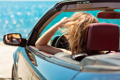 Happy and carefree woman in the car on the beach Stock Images