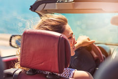 Happy and carefree woman in the car on the beach Stock Photos