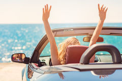 Happy and carefree woman in the car on the beach Stock Image