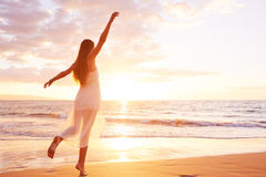 Happy Carefree Woman Dancing on the Beach at Sunset Royalty Free Stock Photo