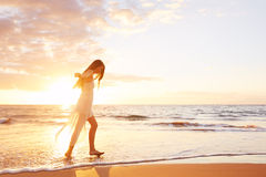 Happy Carefree Woman Dancing on the Beach at Sunset Stock Photo