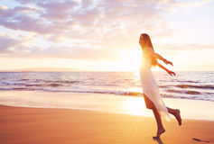 Happy Carefree Woman Dancing on the Beach at Sunset Royalty Free Stock Image