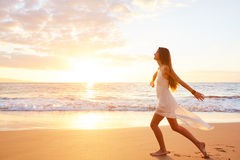 Happy Carefree Woman Dancing on the Beach at Sunset Royalty Free Stock Photos