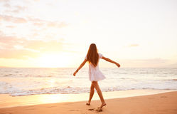 Happy Carefree Woman Dancing on the Beach at Sunset. Happy carefree woman dancing at sunset on the beach. Happy free lifestyle concept stock photography