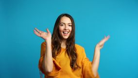 Happy carefree woman dancing on blue background stock video footage