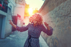 Happy carefree woman dancing on street graded. Happy carefree woman dancing on street in sunset royalty free stock images