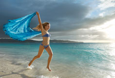 Happy carefree woman dancing at sunset on the tropical beach. Royalty Free Stock Photo