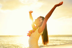 Happy carefree woman free in Hawaii beach sunset. Beautiful woman in the golden sunshine glow of sunset with arms outspread and face raised in sky enjoying royalty free stock photo