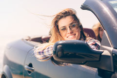 Happy and carefree woman in the car on the beach Stock Photography