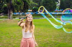 Happy carefree young woman blowing soap bubbles royalty free stock images