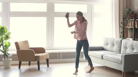 Happy carefree young woman dancing listen to music on smartphone. Happy carefree young woman dancing alone in modern living room with big window listen to music stock footage