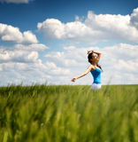 Happy carefree young woman in a green wheat field Stock Photography