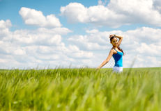 Happy carefree young woman in a green wheat field Royalty Free Stock Image
