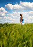 Happy carefree young woman in a green wheat field Stock Photo