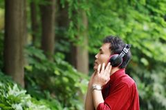 Happy careless free Asian Chinese man is listening to music and wearing a earphone. Happy handsome careless free Asian Chinese man in red shirt is listening to royalty free stock images