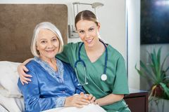 Happy Caretaker With Arm Around Senior Woman At Royalty Free Stock Photos