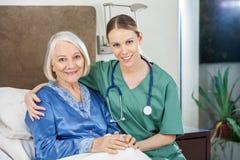 Happy Caretaker With Arm Around Senior Woman At. Portrait of happy female caretaker with arm around senior women at nursing home royalty free stock photos