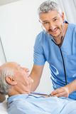 Happy Caretaker Examining Senior Man With Stock Photo