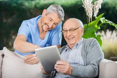 Happy Caretaker And Senior Man Using Tablet PC. Happy male caretaker and senior men using tablet PC at nursing home porch royalty free stock photos