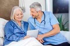 Happy Caretaker With Senior Woman Using Digital Stock Image