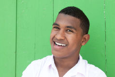 Happy caribbean guy in front of a green wall Stock Photography