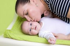 Happy caring mother holding a smiling baby girl and kisses her on changing pad. stock photography