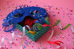 Happy carnival feeling. Praparing for carnival with colorful equipmant and blue mask. The pink background and other color gives party vibes to the image Royalty Free Stock Photography