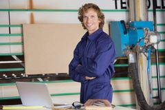 Happy Carpenter With Arms Crossed At Table Stock Image