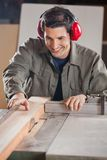 Happy Carpenter Cutting Wooden Plank With Tablesaw Stock Photo