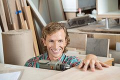 Happy Carpenter Drilling Wood In Workshop Royalty Free Stock Photos