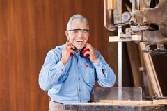 Happy Carpenter Holding Ear Protectors By Bandsaw Royalty Free Stock Images