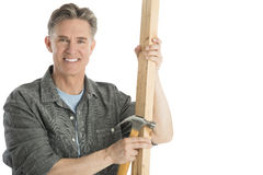 Happy Carpenter Holding Hammer And Plank. Portrait of happy male carpenter holding hammer and plank isolated on white background Stock Photo