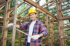 Happy Carpenter Holding Measure Tape At Royalty Free Stock Image