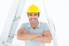 Happy carpenter leaning on step ladder Royalty Free Stock Photo