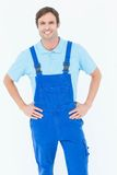 Happy carpenter in overalls with hands on hip Stock Photos
