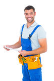 Happy carpenter in overalls holding clipboard Stock Images